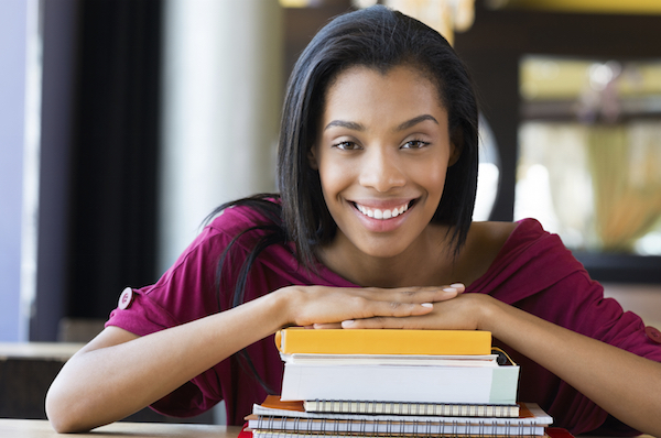 Closeup shot of young woman lies on stack of books. Happy female student smiling and looking at camera. Shallow depth of field with focus on young african woman rests on stack of books.